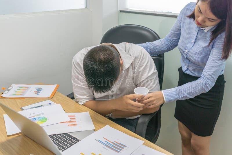 A mulher do escritório traz a medicina ao workmate no escritório fotos de stock