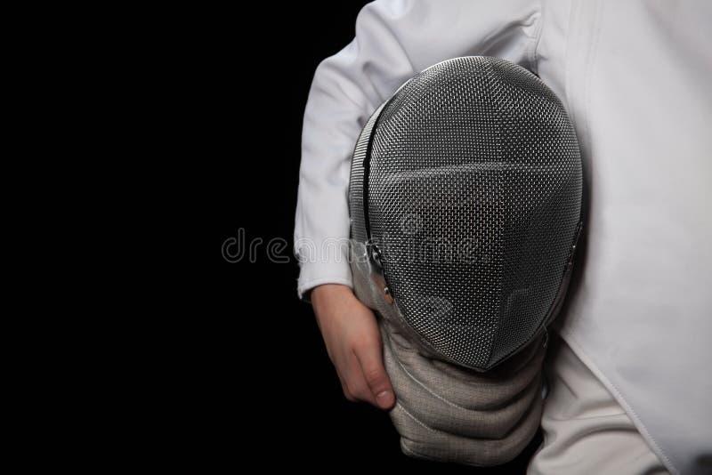 A mulher do esgrimista guarda seu traje de cerco branco vestindo disponivel do capacete Isolado no fundo preto fotos de stock royalty free