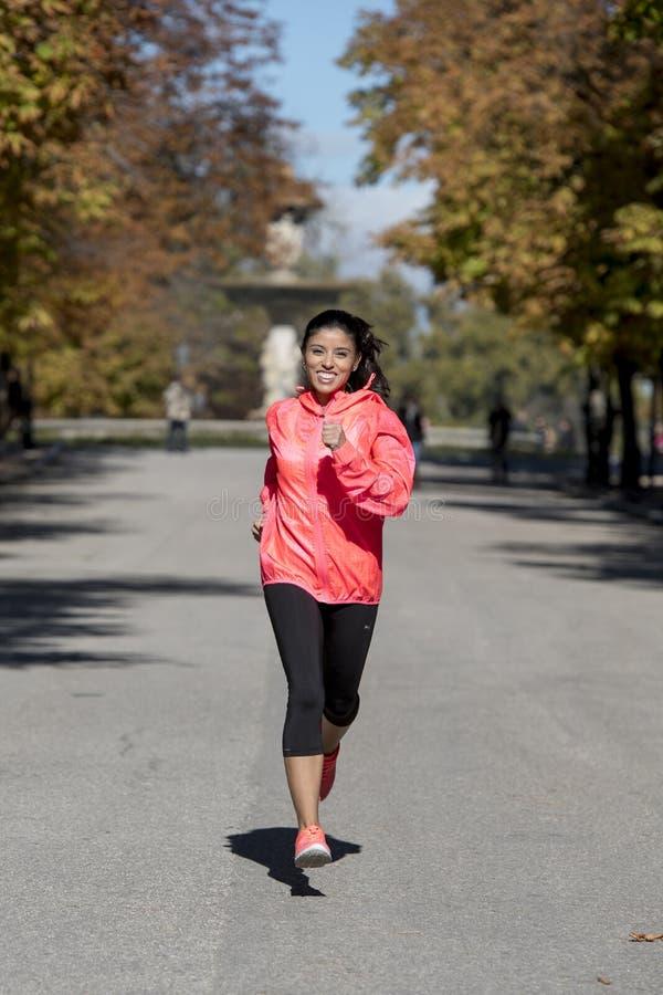 Mulher do esporte do corredor no corredor e no treinamento do sportswear do outono em movimentar fora o exercício no sorriso do p imagem de stock royalty free