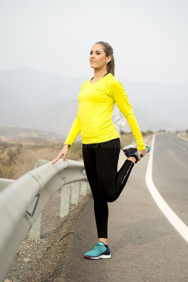 Mulher do esporte que estica o músculo do pé após ter corrido o exercício na estrada asfaltada com paisagem seca do deserto na se imagens de stock royalty free