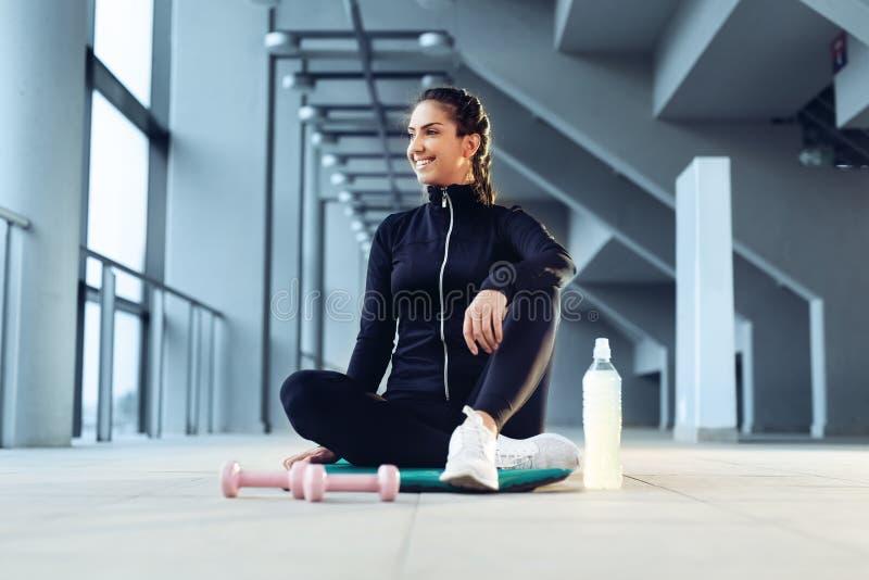 Mulher do esporte que senta-se e que descansa após o exercício ou o exercício no gym da aptidão foto de stock royalty free