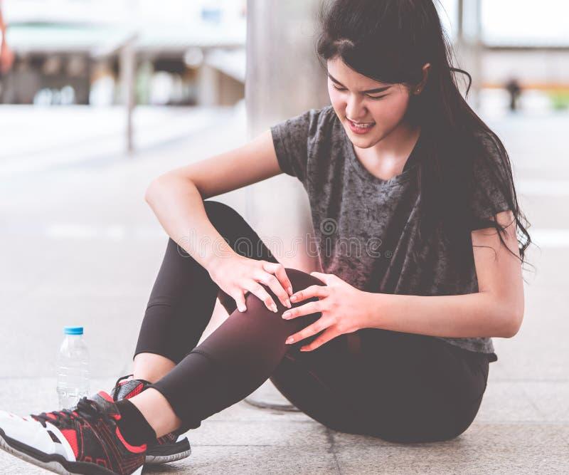 Mulher do esporte que tem um ferimento em seus pés do joelho fotos de stock royalty free