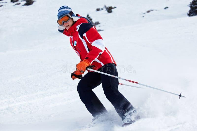 A mulher do esqui gira sobre a inclinação foto de stock