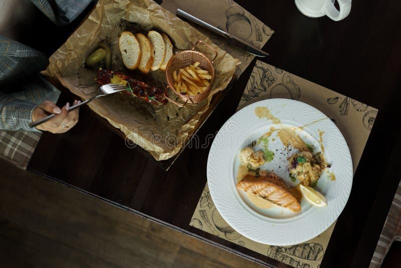 A mulher do estilo de vida come os peixes tartare Alimento saudável e saboroso da carne crua Close-up das mãos fêmeas Grande saqu imagens de stock