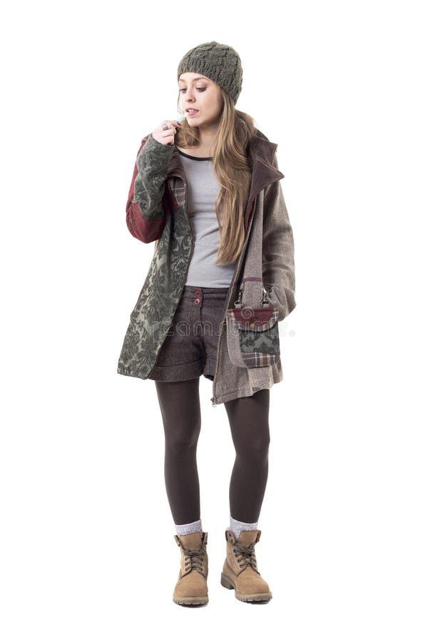 Mulher do estilo do moderno na roupa morna usando o e-cigarro híbrido do cigarro elétrico da audição fotos de stock royalty free