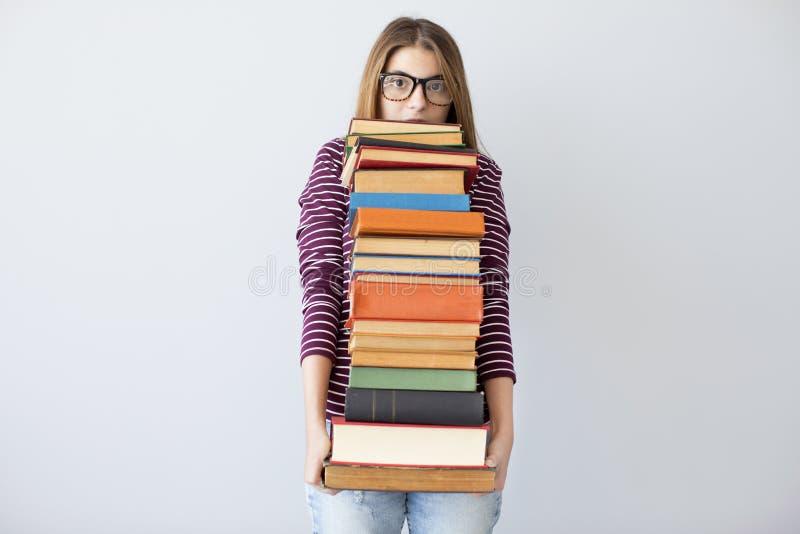 Mulher do estudante que guarda livros da pilha imagem de stock
