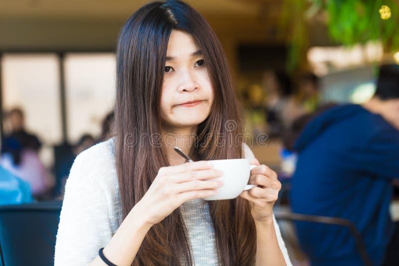 Mulher do estudante que guarda um copo do café do latte em suas mãos no libr fotos de stock