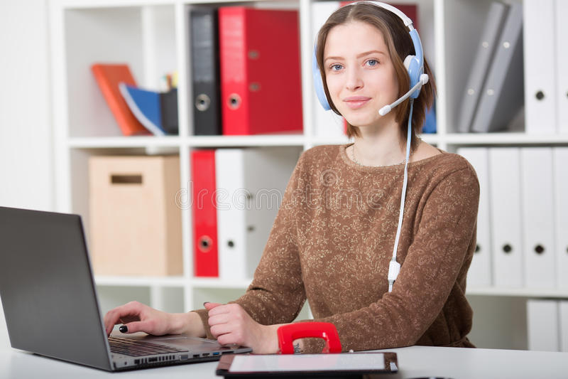 A mulher do estudante usa uns auriculares com um microfone para a universidade de aprendizagem em linha foto de stock royalty free