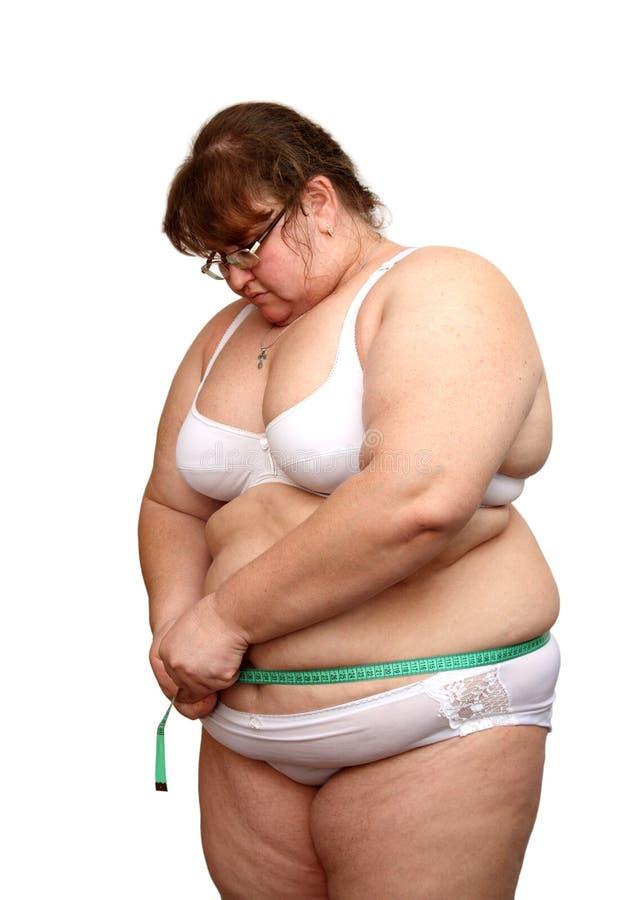 A mulher do excesso de peso mede seu estômago fotografia de stock royalty free