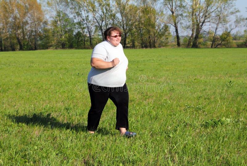Mulher do excesso de peso que funciona no prado imagens de stock royalty free