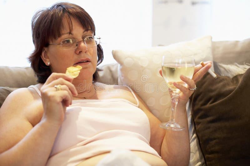 Mulher do excesso de peso que relaxa no sofá fotografia de stock royalty free