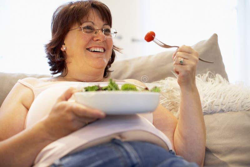 Mulher do excesso de peso que relaxa no sofá fotos de stock royalty free