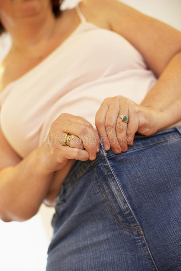 Mulher do excesso de peso que tenta prender calças fotografia de stock