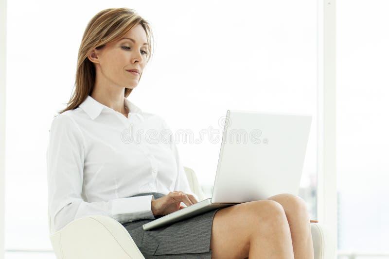 Mulher do executivo empresarial que usa o portátil no lugar contemporâneo fotos de stock royalty free
