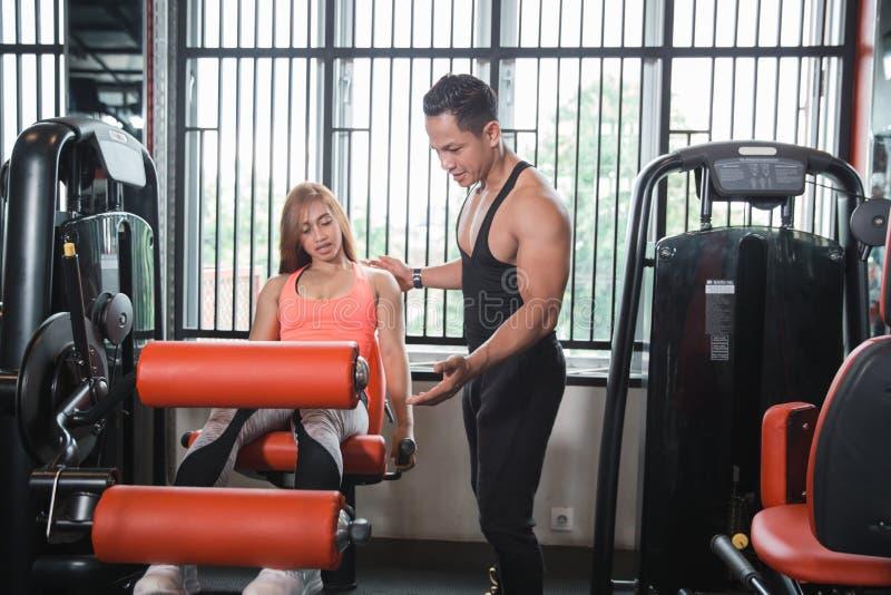 Mulher do exercício do exercício da extensão do pé do Gym com instrutor imagem de stock