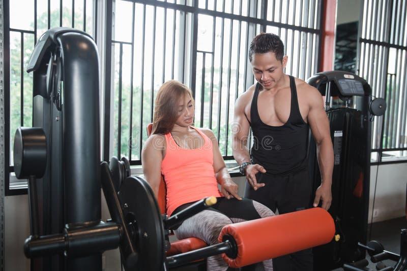 Mulher do exercício do exercício da extensão do pé do Gym com instrutor pessoal fotos de stock royalty free