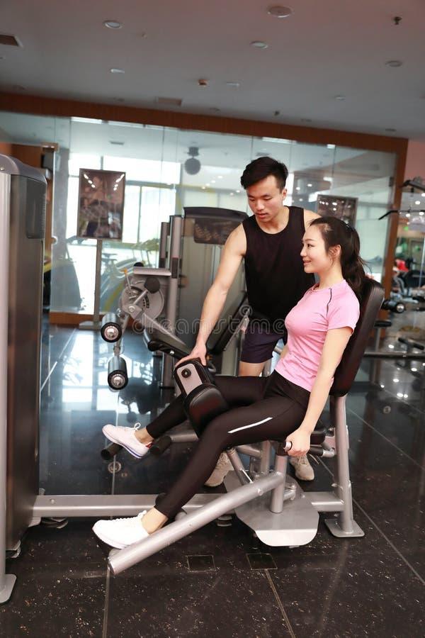 Mulher do exercício do exercício da extensão do pé do Gym interna Bonito, imprensa imagem de stock royalty free