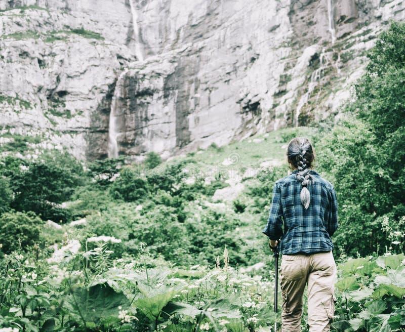Mulher do explorador que anda às cachoeiras no penhasco alto imagens de stock royalty free