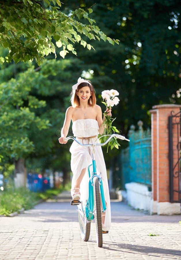 A mulher do fantoche monta uma bicicleta do vintage com o ramalhete das peônias foto de stock royalty free