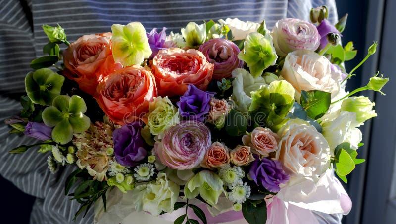 Mulher do florista que guarda um arranjo de flor bonito em um fundo floral do florista foto de stock