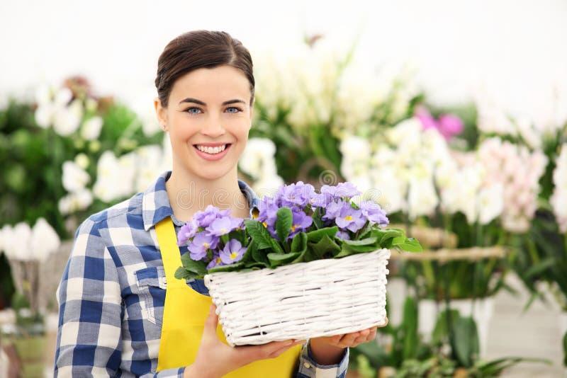 Mulher do florista que sorri com as flores de cesta de vime brancas fotografia de stock