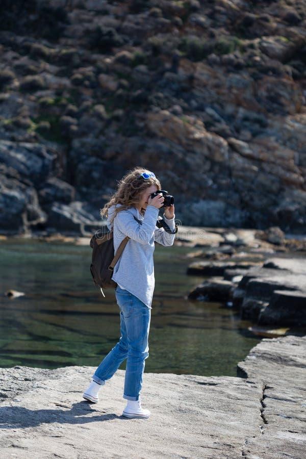 Mulher do fotógrafo no revestimento e em calças de brim cinzentos fotografia de stock royalty free