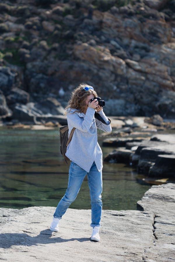 Mulher do fotógrafo no revestimento e em calças de brim cinzentos imagem de stock