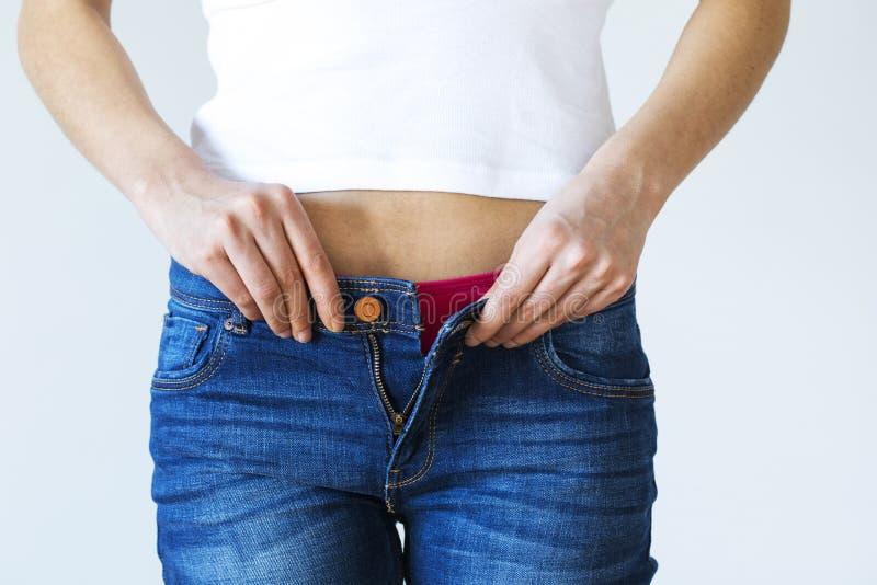 Mulher do ganho de peso que obtem calças de brim vestindo vestidas fotografia de stock