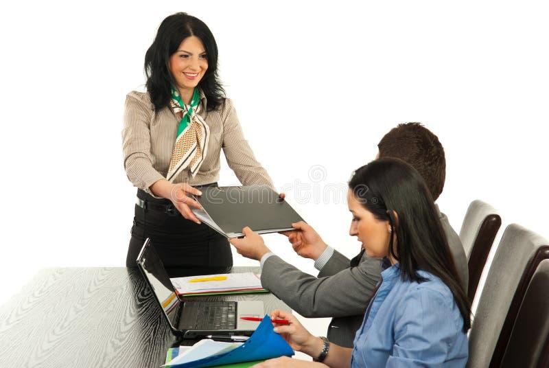 A mulher do gerente dá o dobrador ao empregado imagem de stock