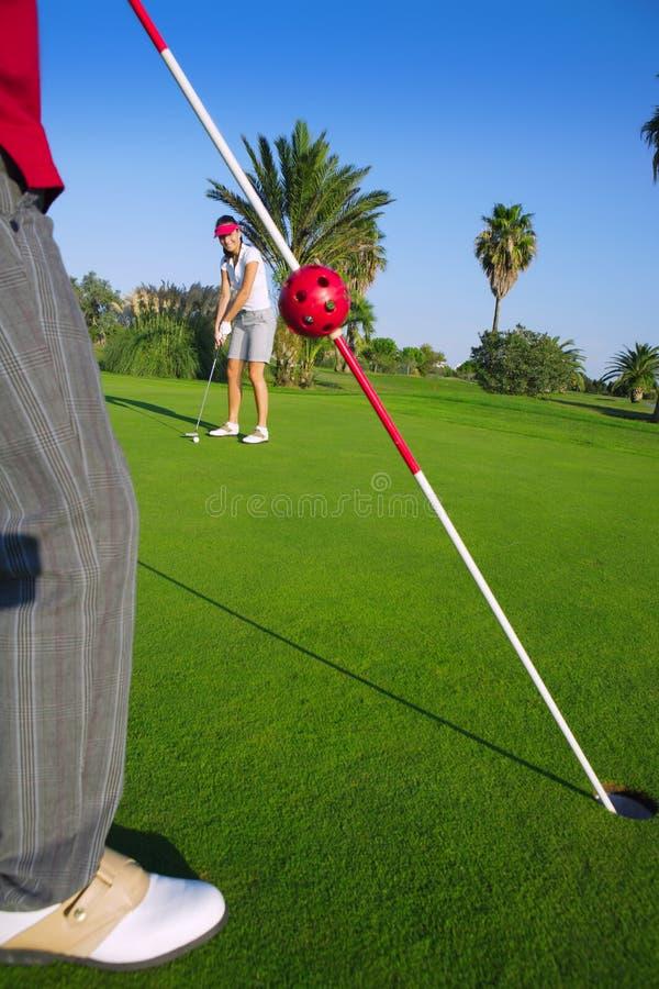 A mulher do golfe que põr a esfera e o homem do gol prende a bandeira fotografia de stock