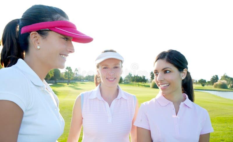 Mulher do golfe três em um curso da grama verde da fileira imagens de stock