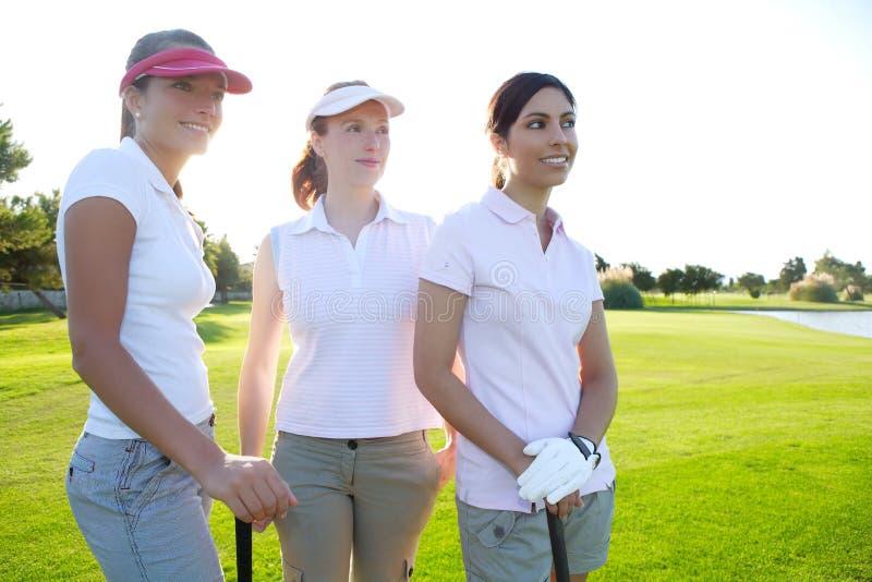 Mulher do golfe três em um curso da grama verde da fileira imagem de stock royalty free
