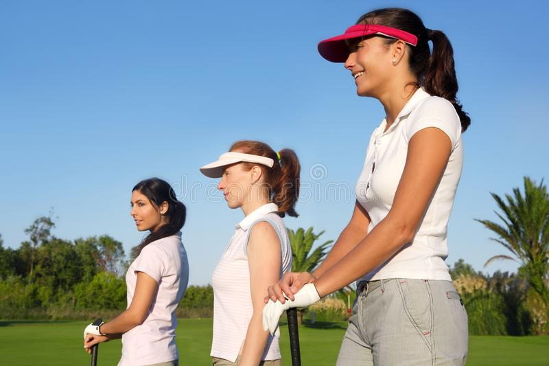Mulher do golfe três em um curso da grama verde da fileira foto de stock royalty free