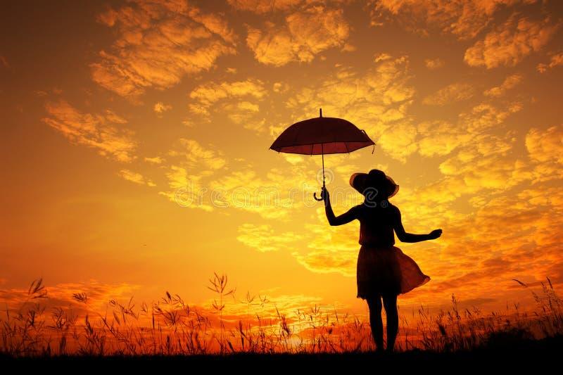 A mulher do guarda-chuva saltam e a silhueta do por do sol imagens de stock