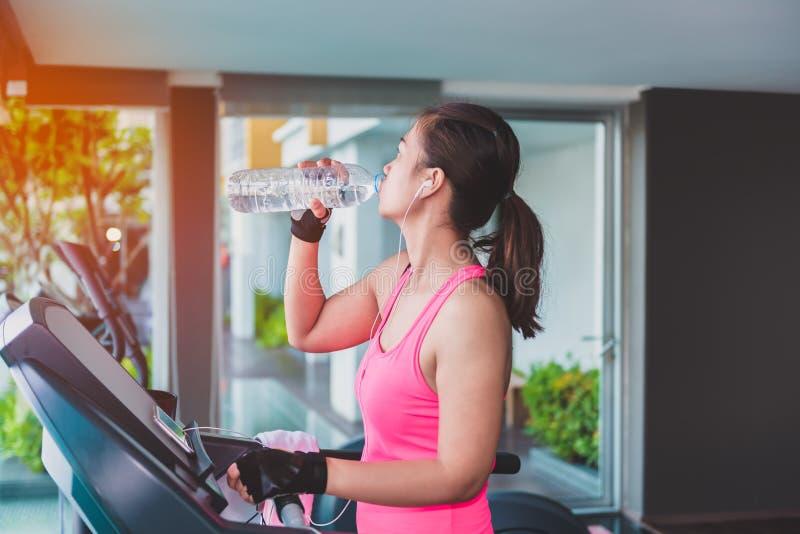 Mulher do Gym que dá certo a água potável pelo machi da aptidão do moonwalker fotos de stock royalty free