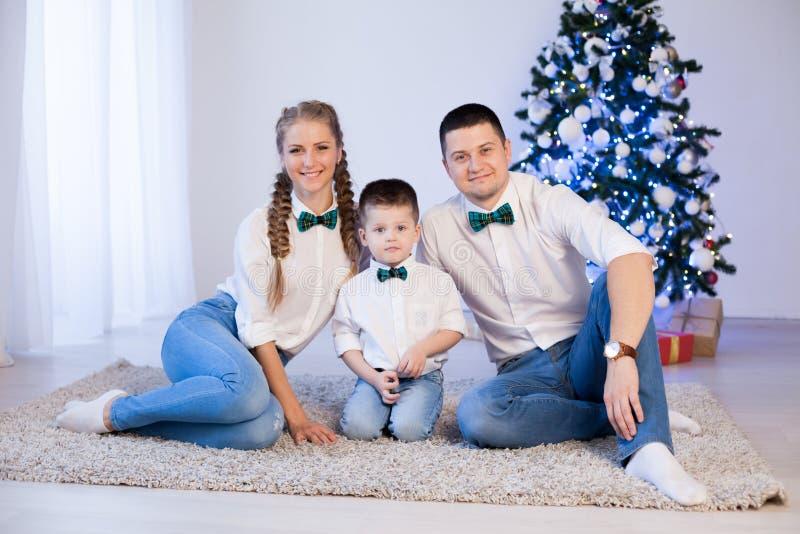 Mulher do homem e filho novo que sentam-se no inverno do feriado dos presentes do ano novo de árvore de Natal foto de stock royalty free