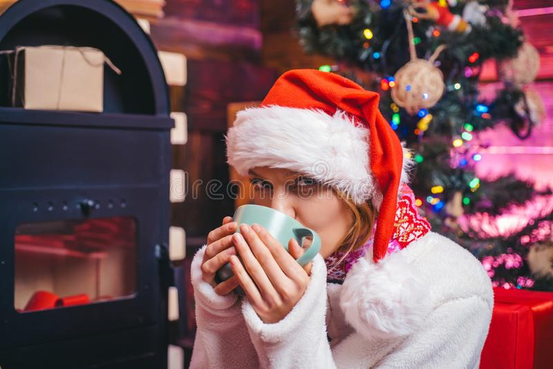 Mulher do inverno que veste o chapéu vermelho de Papai Noel Menina do ano novo Árvore de Natal em casa Presente do Natal Mulher e fotografia de stock