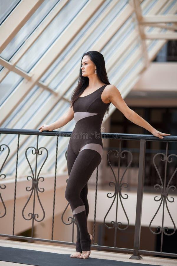 Mulher do iogue em um fato-macaco escuro que sretching após o grande exercício Jovem mulher bonita nova no sportswear que faz o e foto de stock royalty free