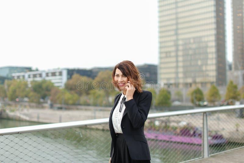 a mulher do journalista no negócio veste a fala no smartphone fotografia de stock