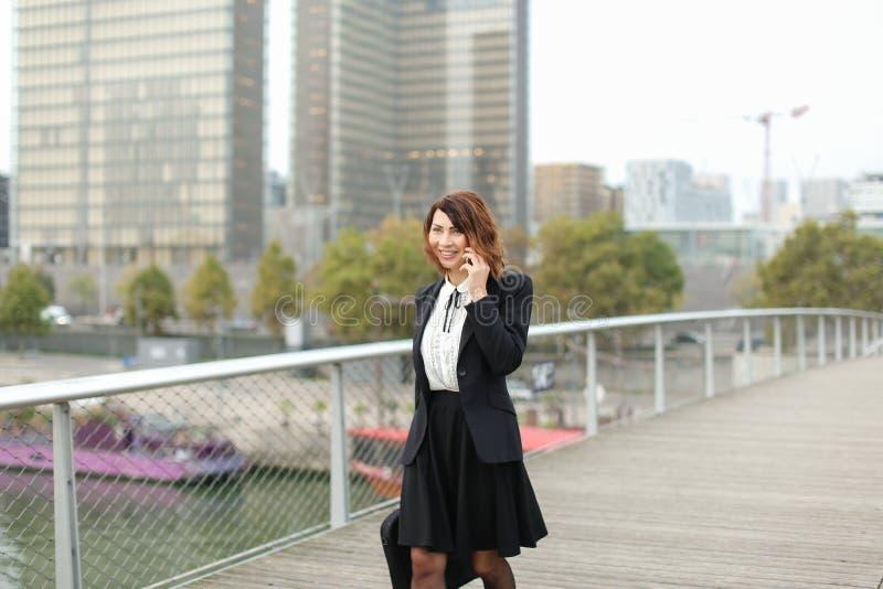 a mulher do journalista no negócio veste a fala no smartphone fotos de stock royalty free