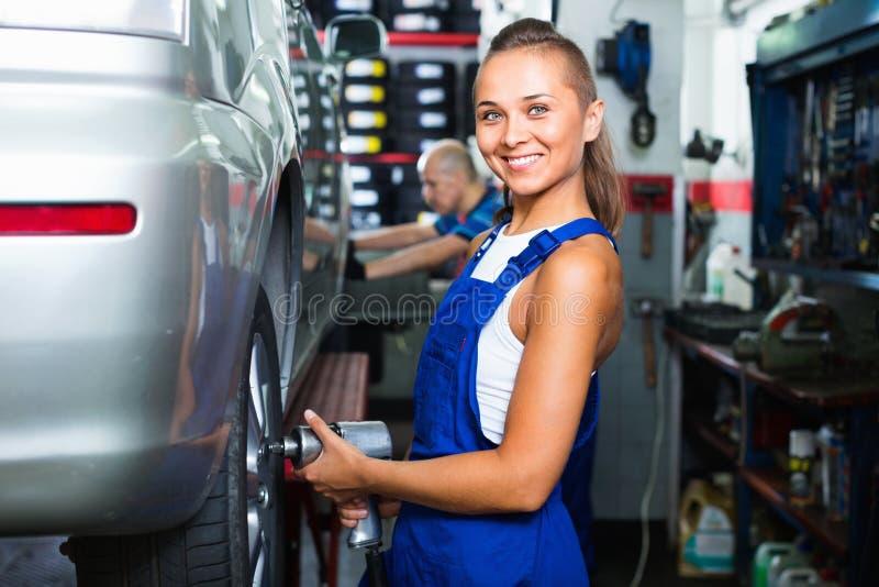 Mulher do mecânico que trabalha na maquinaria do controle do equilíbrio da roda fotografia de stock royalty free