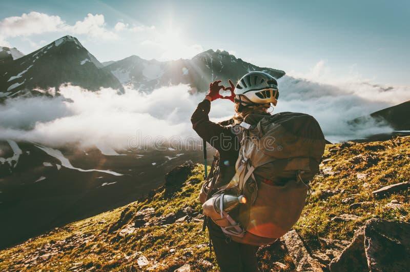 A mulher do mochileiro entrega mostrar a forma do coração que aprecia montanhas imagem de stock royalty free