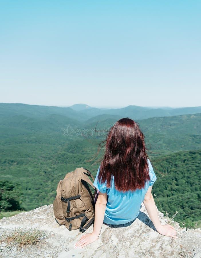 Mulher do mochileiro que senta-se no pico do penhasco no verão imagens de stock royalty free