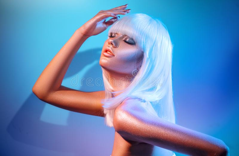 Mulher do modelo de forma em sparkles brilhantes coloridos e nas luzes de néon que levantam no estúdio foto de stock royalty free