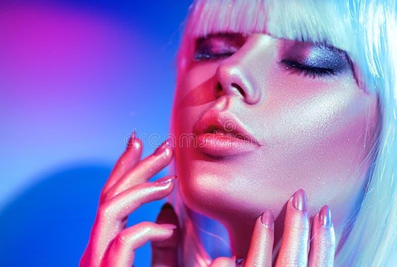 Mulher do modelo de forma em sparkles brilhantes coloridos e nas luzes de néon que levantam no estúdio fotos de stock royalty free