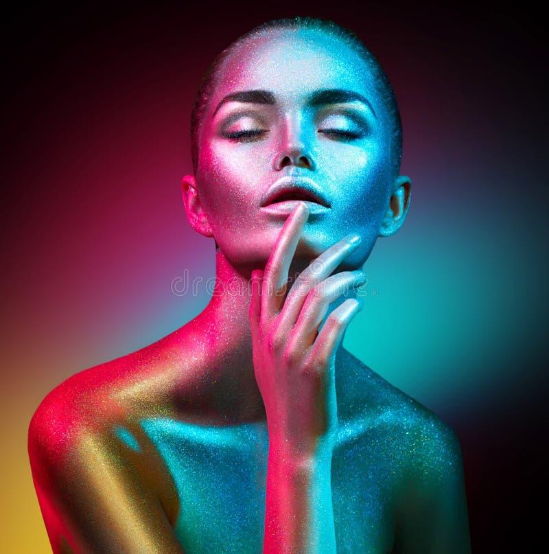Mulher do modelo de forma em sparkles brilhantes coloridos e nas luzes de néon que levantam no estúdio, retrato da menina 'sexy'  imagem de stock