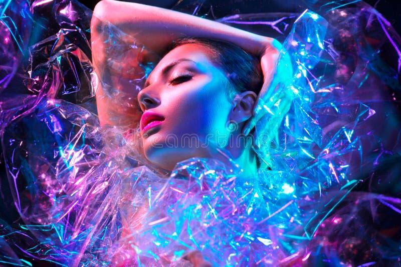 Mulher do modelo de forma nas luzes de néon brilhantes coloridas que levantam no estúdio através do filme transparente Retrato da imagem de stock royalty free