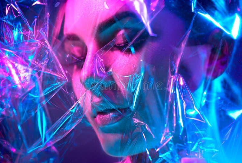 Mulher do modelo de forma nas luzes de néon brilhantes coloridas que levantam no estúdio através do filme transparente Retrato da fotos de stock royalty free