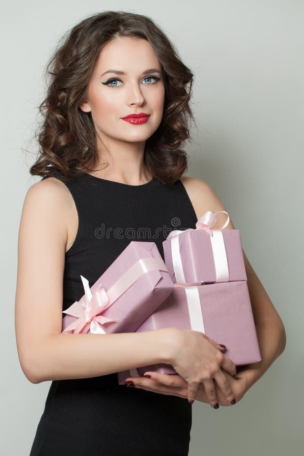 Mulher do modelo de forma que guarda presentes imagem de stock