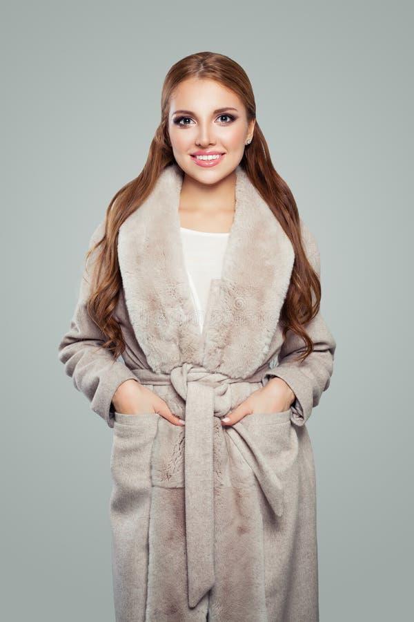 Mulher do modelo de forma que veste o revestimento bege que sorri e que levanta no fundo cinzento imagens de stock
